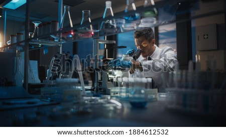 Medical Development Laboratory: Scientist Looking Under Microscope, Analyzes Petri Dish Sample. Pharmaceutical Lab with Specialists Conducting Medicine, Biotechnology Research. Evening Work Foto stock ©