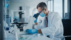 Medical Development Laboratory: Scientist Wearing Face Mask Looking Under Microscope. He Mix Petri Dish Sample. Specialists Working on Medicine, Biotechnology Research in Advanced Pharma Lab