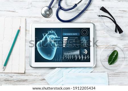 Medical diagnostics in hospital. Tablet computer with medical app interface on screen. Doctor workplace with stethoscope and cardiogram on wooden desk. Digital technology in cardiology clinic. Foto stock ©
