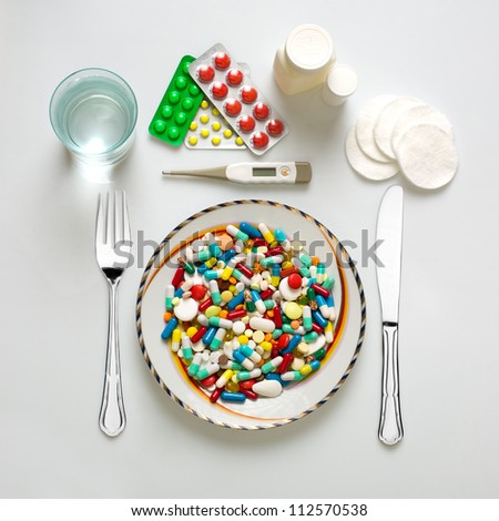 Medical dinner set with silverware and pills - stock photo
