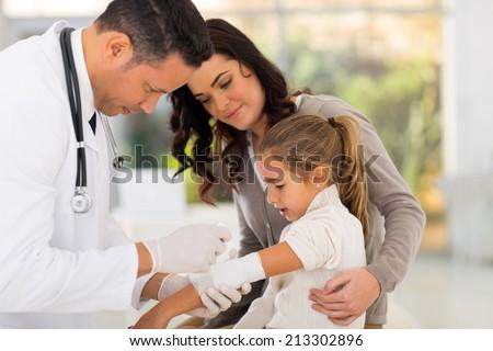 medical doctor bandaging injured patient in hospital