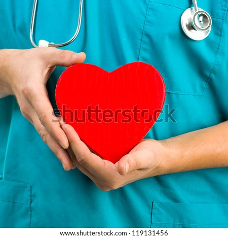 medical doctor holding a heart symbol  on white background - stock photo