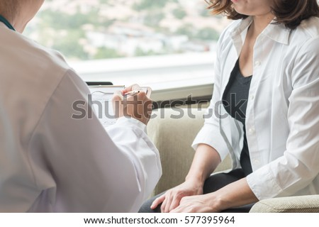 Medical doctor in office white uniform gown coat working consulting woman patient having exam: Physician hand writing clinical discharge form healthcare: Hospital/ clinic reliable professional concept