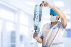 medical doctor looking at x-ray picture of spinal column in hospital with copy space