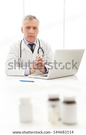 Medical doctor.Mature  doctor sitting at his working place with the medicines on the foreground