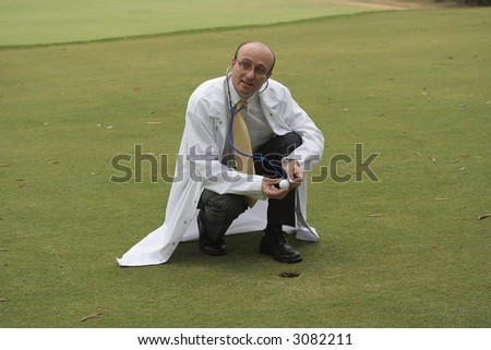 Medical doctor on the golf course checking a gold ball with his stethoscope, in the hope of helping you improve your game