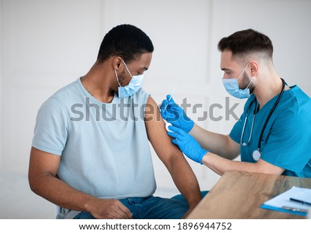 Medical doctor or nurse giving coronavirus vaccine shot to African American male patient at clinic. Young black man in face mask getting covid-19 vaccine, participating in immunization campaign