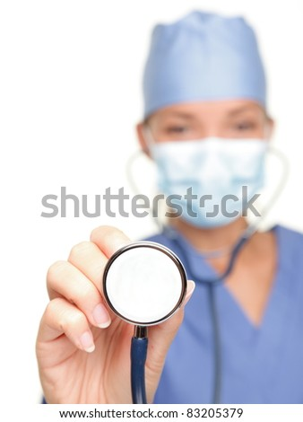Medical doctor showing stethoscope close up isolated on white background. Female nurse or doctor wearing surgical mask and hat. Woman model.