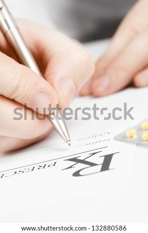 Medical doctor signing prescription with  silver pen on a table