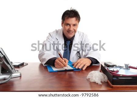 Medical doctor sitting at desk writing with pen on a  medical form.  He is looking up and smiling and listening.