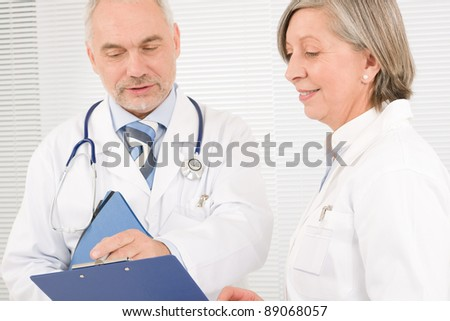 Medical doctor team senior woman and mature man holding folders