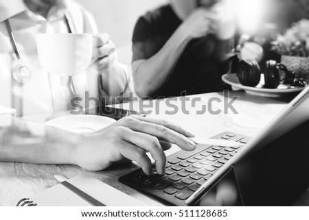 Medical doctor team taking coffee break.using digital tablet docking keyboard and smart phone on marble desk.listen music,filter film effect,black white