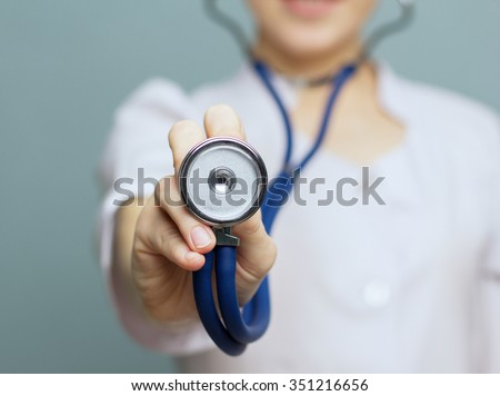 Medical doctor woman   on a blue background holding a stethoscope focus on the stethoscope