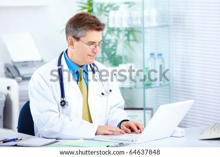 Medical doctor working with laptop in the office - stock photo