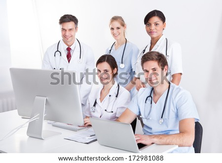 Medical Doctors Working On Computer And Laptop In Hospital