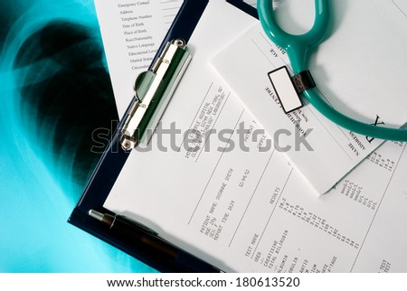 Medical documents (blood test, prescription and medical questionnaire) with a stethoscope on Xray photo of lungs