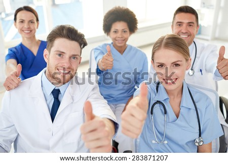 medical education, health care, gesture people and medicine concept - group of happy doctors on seminar in lecture hall at hospital showing thumbs up