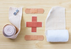 Medical elastic bandage and medical gauze bandage on wood table.