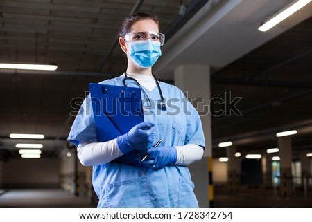 Medical EMS worker wearing PPE uniform,safety goggles and face mask,holding clipboard at mobile test center site,PCR Coronavirus COVID-19 virus disease detection in drive-thru check  control facility