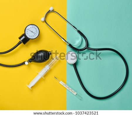 Medical equipment on a colored paper background. Stethoscope, syringe, thermometer, tonometer. Top view, flat lay.