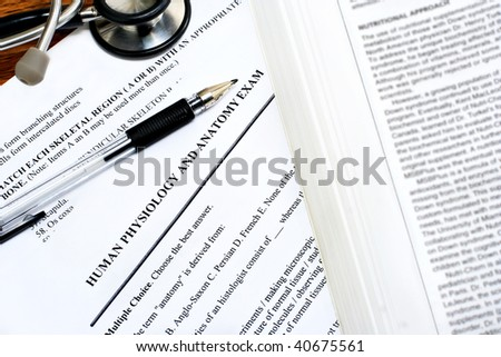 Medical exam papers on a desk with a pen, stethoscope and a medical book.  Concept of becoming a doctor.