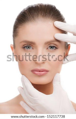 Medical exam. Portrait of beautiful young woman looking at camera while hands in gloves examining her face