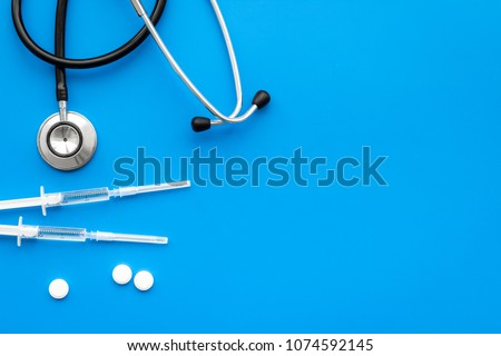 Medical examination and treatment concept. Stethoscope, syringe, pills on blue background top view copy space