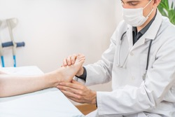 Medical examination. Medical examination on patient leg in clinic. Traumatology. Hospital. Injured. Therapy. Care. Face mask.