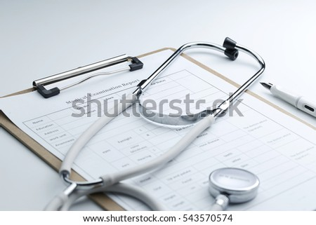 Medical examination report and stethoscope on white desktop #543570574