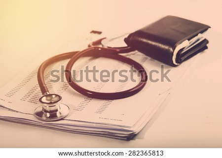 Medical expense concept. Stethoscope on record list with old wallet. Vintage filter.