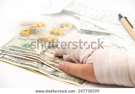 Medical expense with broken or splint hand with us dollars currency, bills and pen on white background