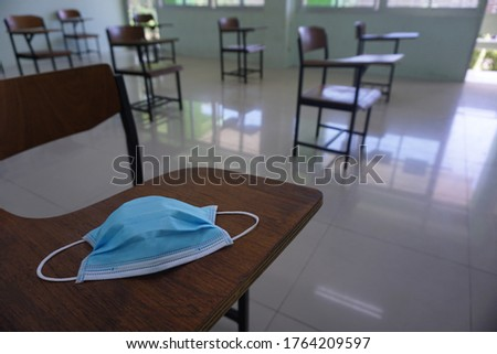 Medical face blue mask on the wood lecture chairs place distancing in the empty classroom. Concept during the Coronavirus disease COVID-19 outbreak in the 2020s. Back to school concept.