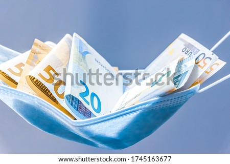 Medical face mask holding money inside of it, on a light background. World coronavirus pandemic losses concept.  50, 20 and five euro bills lie in a hammock made of medical mask.