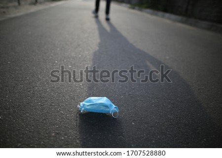 Medical face mask on the floor in the street.Disposable Face Mask.Used Surgical masks haphazardly strewn on pavement.Improperly discarding used face mask. Lost face mask at pavement
