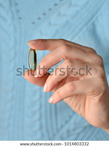 Medical. Female hand with clear shiny yellow Vitamin E capsule on blue background. Омега 3. Витамин Е Сток-фото ©