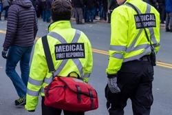 Medical first responders walking along a road wearing black wool stocking caps, yellow reflective coats with medical first responder in grey letters uniform.