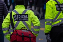 Medical first responders walking along a road wearing black wool stocking caps, yellow reflective coats with medical first responder in grey letters and a cross.One EMT is carrying a red first aid kit