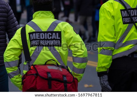 Medical first responders walking along a road wearing black wool stocking caps, yellow reflective coats with the medical first responder in grey letters and across. The EMT is carrying a first aid kit Stock photo ©