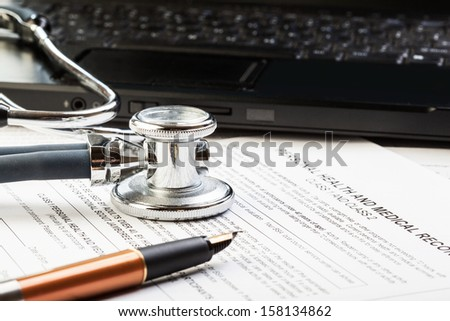 Medical form, stethoscope, laptop and pen