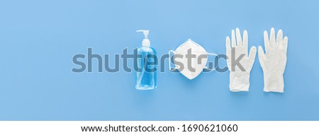 Medical gloves mask and alcohal gel for protecting infection during Coronavirus pandemic top view on light blue banner background with copy space