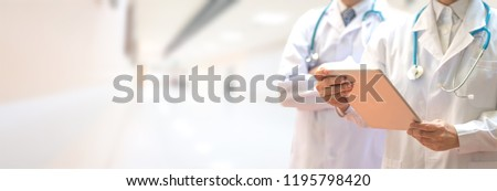 Medical healthcare doctor team concept. Physicians in white gown and stethoscope, hand holding computer tablet on blur background corridor hospital for copy space.