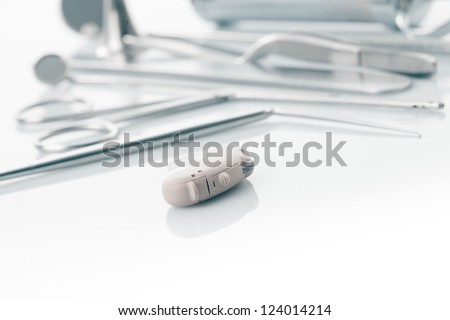 Medical instruments for ENT doctor on white and hearing aid, alternative to surgery
