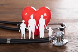 Medical Insurance Concept With Family Cut-out And Stethoscope On Wooden Desk