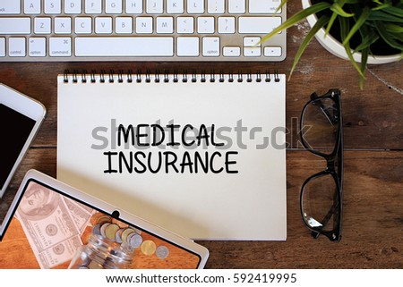 Medical Insurance concept with smartphone, keyboard, glasses, keyboard on wooden table