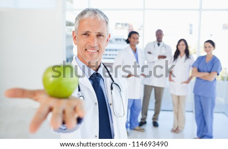 Medical interns in the background looking at their doctor who is holding an apple