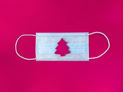 Medical mask and wooden christmas tree on a magenta background.