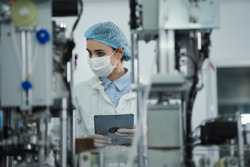 Medical mask factory, a team of medical professionals, a wide range of industries, programming and manipulation of high-tech facility robots Scientist Sterile clothing, lab work