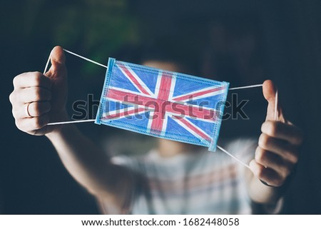 medical mask in hands of man, with the flag of  Great Britain painted. Copy space
