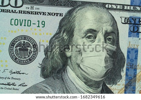 Medical mask on a banknote of 100 dollars, concept of the global financial crisis. Medical mask or surgical mask on american money. COVID-19 coronavirus in USA. Doctor mask protects against COVID-19.