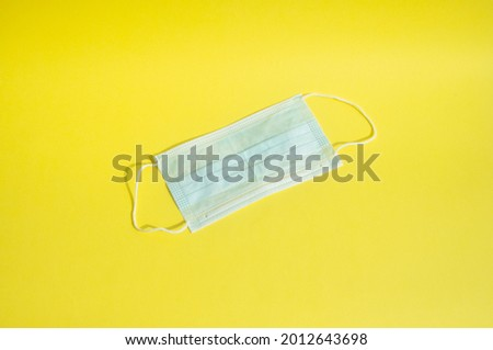 Medical mask on a yellow background. Medical masks are effective for filtering the covid-19 virus Stok fotoğraf ©